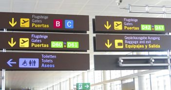 Malaga Airport display giving directions in three languages